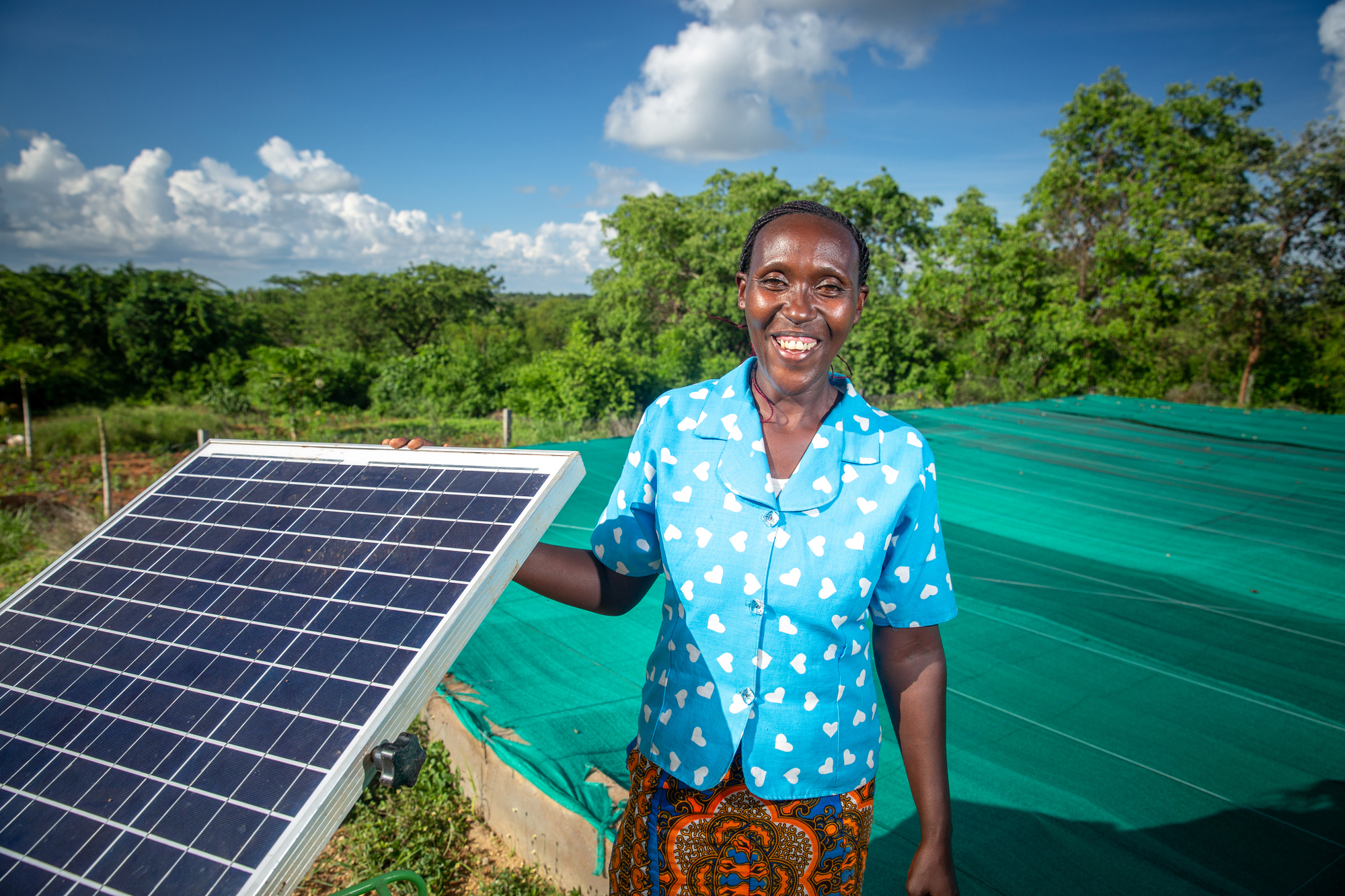 Women in Kenya holding solar panel