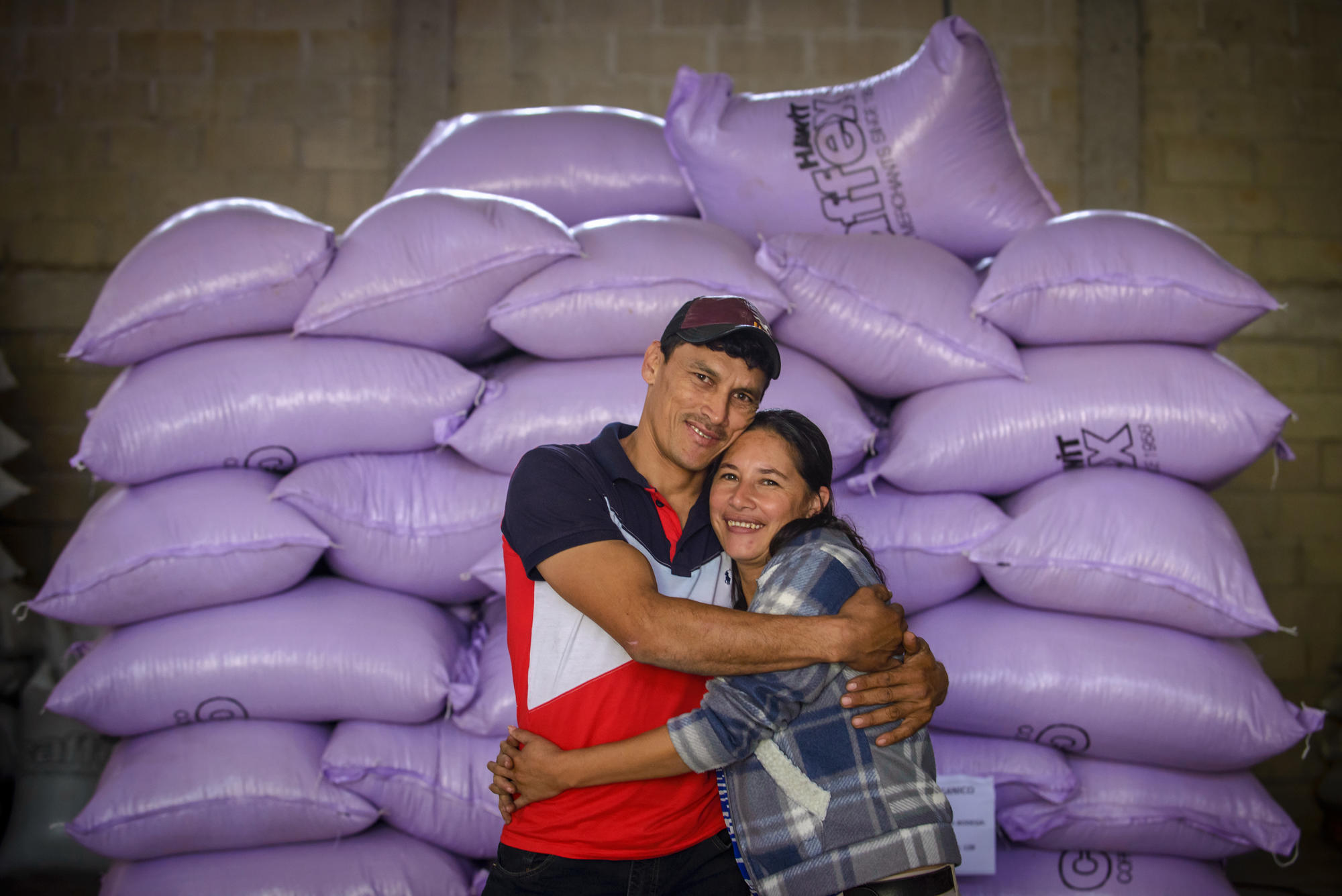 couple hugging each other and behind them are bags of roasted coffee beans