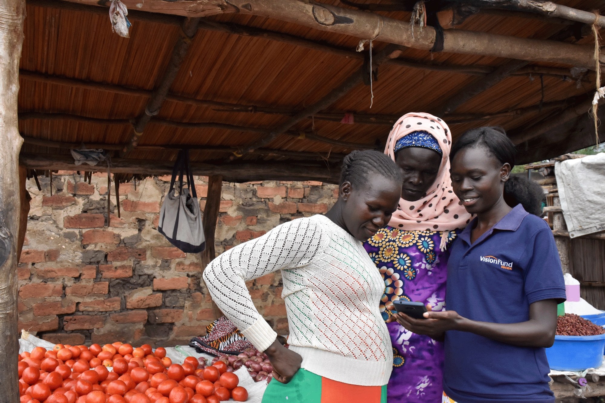 VisionFund loan officer shows client how to make repayments via mobile money