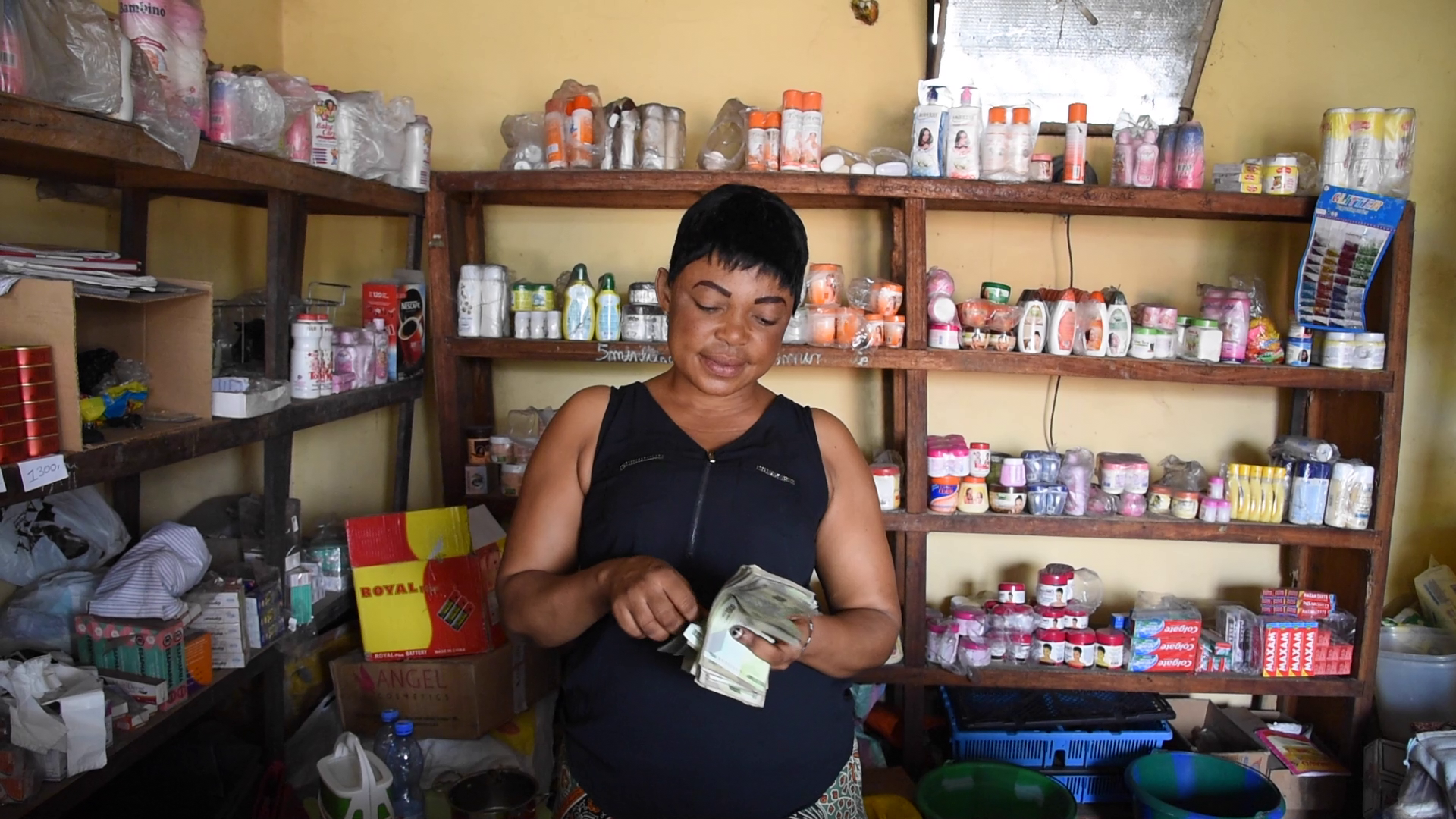 Innocente counting money in her shop