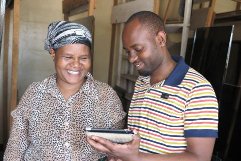 VisionFund loan officer collecting client data via tablet