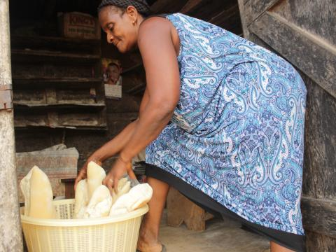 Mercy standing on the stairs of her home in Ghana with bread basket