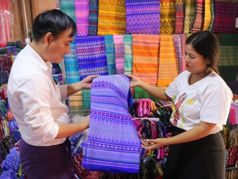 Thin Thin Hlaing showing a client her fabrics she sells in Myanmar