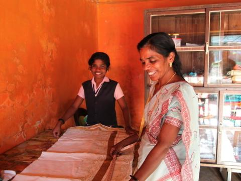 Woman tailor while daughter helps in India
