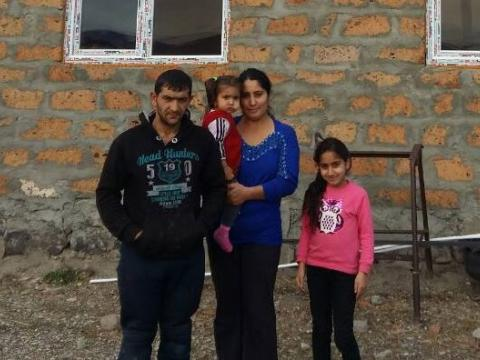 Serb and his family in front of their home with solar panels.