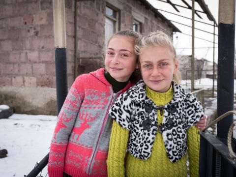 Two sisters standing outside in the snow in front of their home in Armenia