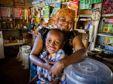 Fatuma and her son in her store that she got a loan to grow.