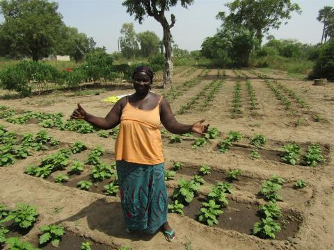 Daba standing with arms open to showcase her thriving gardens.