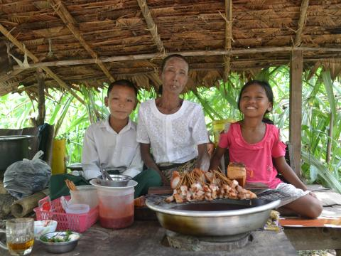 Daw San with her two grandchildren in their home in Myanmar