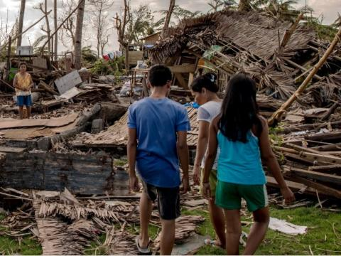 Children walk in the rumble in the aftermath of a typhoon