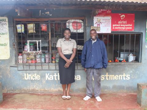 Feston and his VisionFund Malawi loan officer in front of his store.