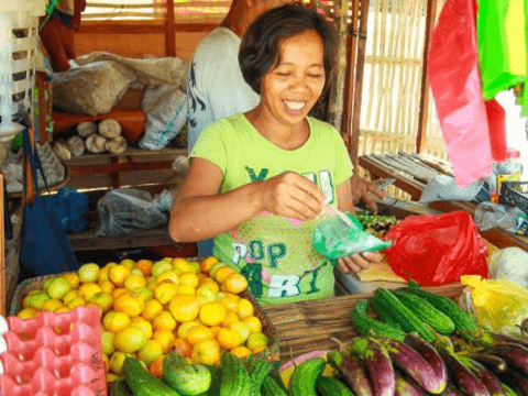 Judith smiling in her vegetable stall in the Philippines.