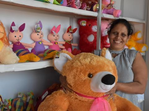 A single-mother of three, Thakshila (36 years) standing with a bear stuff animal in her store.