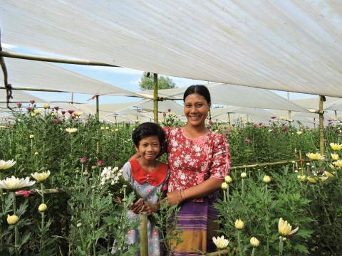 VisionFund client from Myanmar stands in flower garden with her daughter