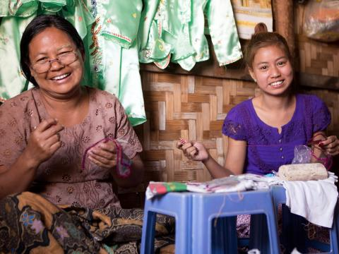 Myint Myint and her daughter working at their seamstress store.