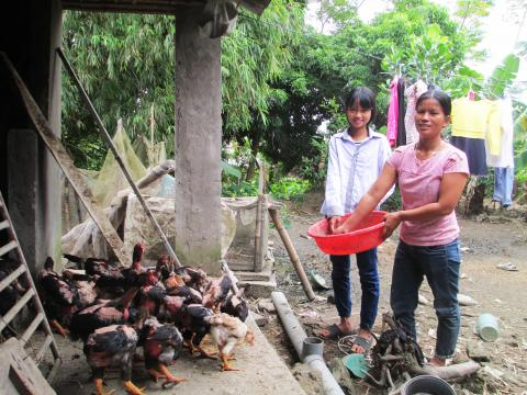 Vu with her daughter feeding their chickens