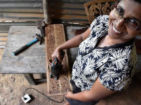 Wijayangani doing the creative side of the woodworking business she owns with her husband, carefully carving out intricate floral designs.
