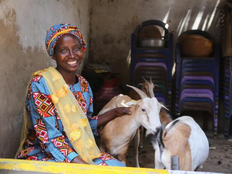 Woman sits with her goats
