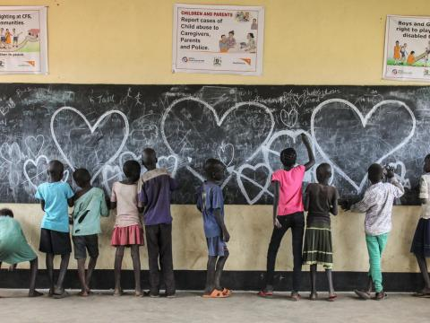 Children draw lovehearts on a chalkboard