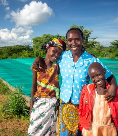 Woman standing beside two children in Kenya