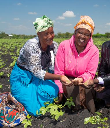 Two women in their field planting seeds with training from agricultural expert
