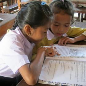 Two young girls ready school book in classroom