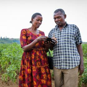 husband and wife looking at mobile phone in farm in Rwanda