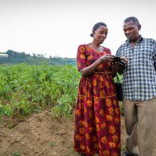 Husband and wife look at mobile phone while standing in farm in Rwanda