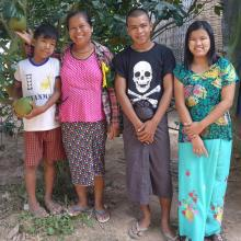 Family in Myanmar standing under a tree