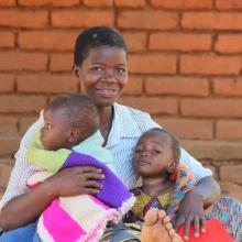 Mother holding two small children in Malawi