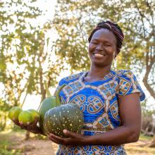 Pastor Jane holding produce from her farm that is thriving in Kenya