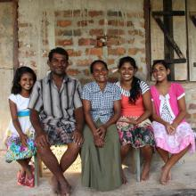 Family sitting in front of their house in Sri Lanka that was built from proceeds from their dairy business.